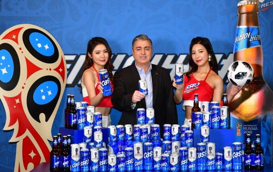 오비맥주 고동우 대표(가운데)와 카스 모델들이 2018 러시아 월드컵에서 한국팀의 선전을 기원하며 '뒤집어버려'의 메시지를 담은 '카스 후레쉬 월드컵 스페셜 패키지'와 함께 기념 촬영을 하고 있다.