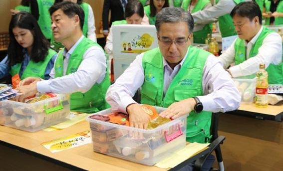 김영상(앞줄 오른쪽) 포스코대우 사장이 인천 송도 사옥에서 회사 임직원들과 함께 한과·생필품·식용품을 포장하고 있다.ⓒ포스코대우
