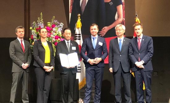 칼스버그 그룹 아나스 루드 욘슨 부사장(왼쪽 네번째)과 ㈜골든블루 김동욱 대표(왼쪽 세번째)가 MOU 협약서를 들고 기념 촬영을 하고 있다.