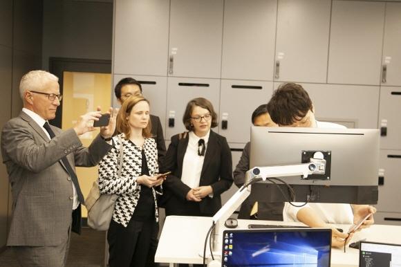 벵트 묄러뢰드 OECD WP-CISP 의장(맨 왼쪽) 일행이 SK텔레콤 5G 스마트오피스에서 5G VDI 도킹 시스템 시연을 보고 있다.ⓒSK텔레콤