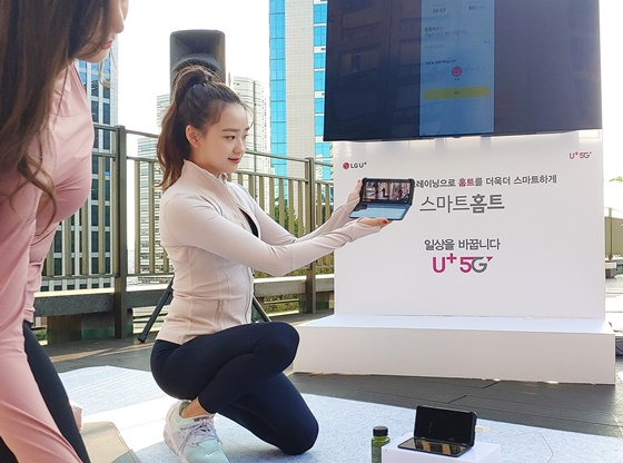 체조 선수 손연재가 LG유플러스 행사에 참석한 고객과 LG V50S ThinQ의 업그레이드된 듀얼스크린을 통해 스마트홈트 콘텐츠 중 하나인 '손연재의 명품바디라인 만들기'를 체험하는 모습. ⓒLGU+