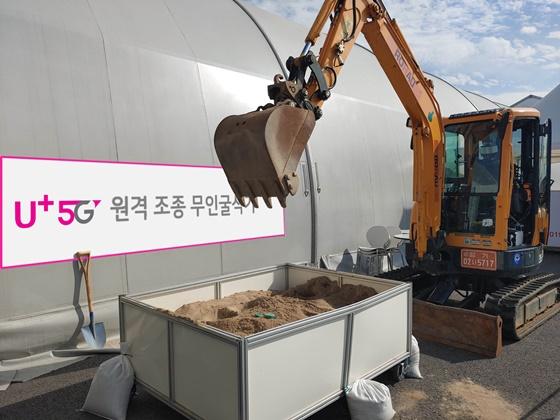 성남 서울공항 전시장 밖에 마련된 작업장에서 5G 무인 굴삭기가 시연을 펼치는 모습. ⓒLGU+