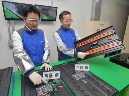 삼성SDI 중대형System개발팀장 허은기 전무(오른쪽)가 ESS용 특수 소화시스템의 효과를 설명하고 있다. 특수 소화시스템이 적용된 ESS 모듈커버에 불을 붙이자 불이 수초 내 꺼져 모듈 커버에 화재 손상이 없었지만(사진 오른쪽) 특수 소화시스템이 적용되지 않은 ESS 모듈커버는 불에 녹아 구멍이 날 정도로 손상을 입었다(사진 왼쪽)