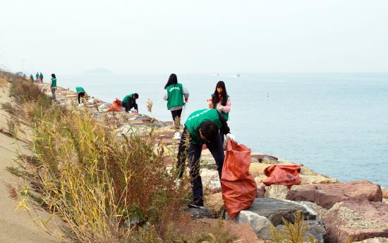 삼천리 임직원과 가족 봉사자들이 시화방조제에서 환경정화 활동을 펼치고 있다.
