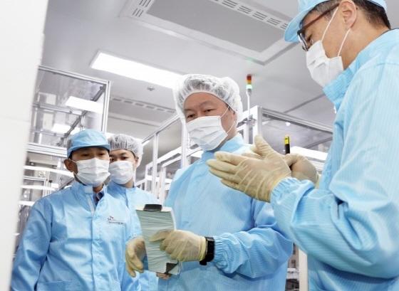 배터리 셀을 든 최태원 회장(가운데)이 김진영 배터리생산기술본부장(오른쪽)으로부터 설명을 듣고 있다.