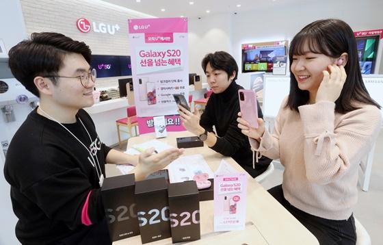 1호 가입자인 최혜원 씨와 2호 가입자인 윤건희 씨가 27일 LG유플러스 서울 종각직영점에서 갤럭시 S20을 개통하고 있는 모습. ⓒLGU+