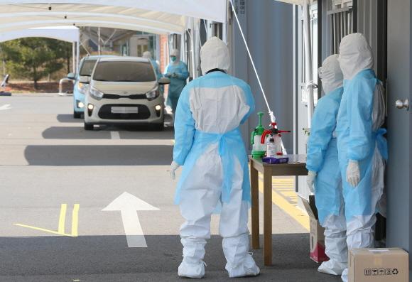경기 김포 장기동 뉴고려병원앞에 마련된 드리이브 스루 선별진료소에서 의료진이 방문자 검체 채취를 준비하고 있다.ⓒ사진공동취재단