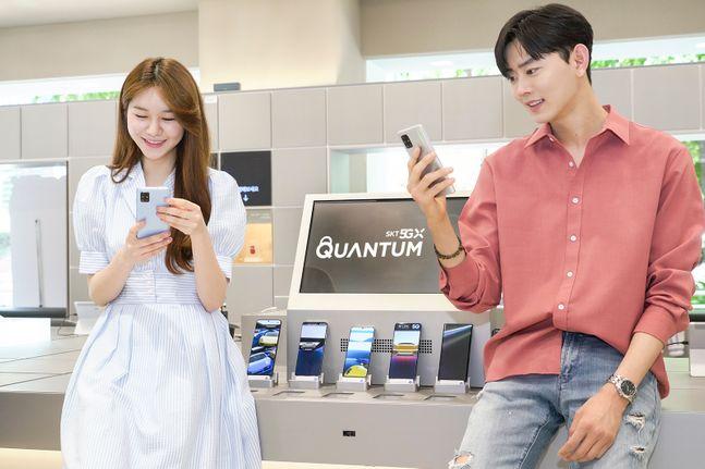 SK텔레콤 모델들이 T월드 매장에서 양자난수생성 칩셋을 탑재한 5G 스마트폰