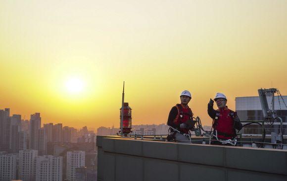 SK텔레콤 홍보모델들이 서울에 위치한 한 빌딩 위에서 5G 기지국을 점검하며 5G 상용화 1주년을 기념해 포즈를 취하고 있다.ⓒSK텔레콤