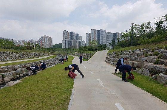원주기업도시 관리공사 현장 롯데건설 직원들이 5일 수변공원에서 환경정화활동을 실시 중인 모습.ⓒ롯데건설