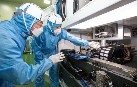 삼성전자 직원(좌)과 이오테크닉스 직원(우)이 양사가 공동 개발한 반도체 레이저 설비를 함께 살펴보고 있다. ⓒ삼성전자