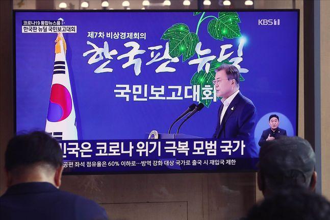 14일 오후 서울 용산구 서울역 역사 내에서 시민들이 문재인 대통령의 한국판 뉴딜 국민보고대회 생중계를 시청하고 있다. ⓒEBN
