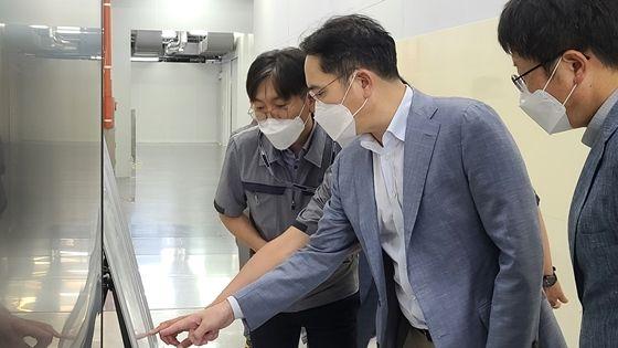 이재용 부회장이 16일 삼성전기 부산사업장에 위치한 전장용 MLCC 전용 생산 공장을 찾아 설명을 듣고 있다. ⓒ삼성전자