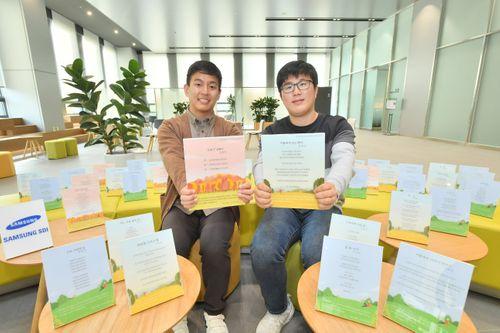 삼성SDI의 비대면 백일장에서 최우수상을 수상한 직원들이 본인의 작품을 들어 보이고 있다. (왼쪽부터 삼성SDI 김현선프로, 장경호 프로).ⓒ삼성SDI